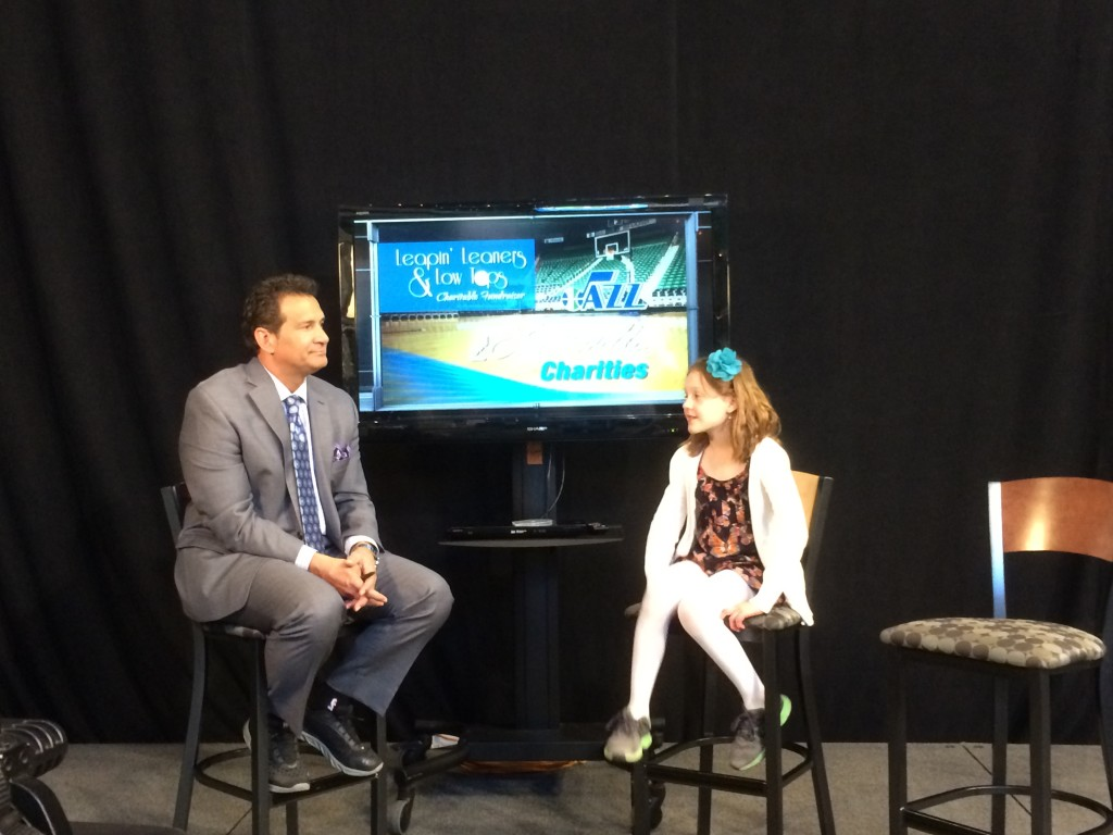 "Here, with no Jazz player to interview, Jazz TV halftime host Alema Harrington interviews a little girl. Alema: ""Did you make your hair like that by braiding it?"""