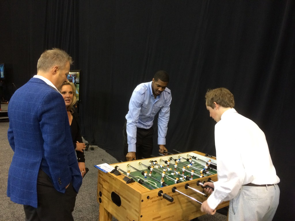 "Jazz owner Greg Miller watches Derrick Favors play foosball. Favors: ""I'm not as good at this game."""