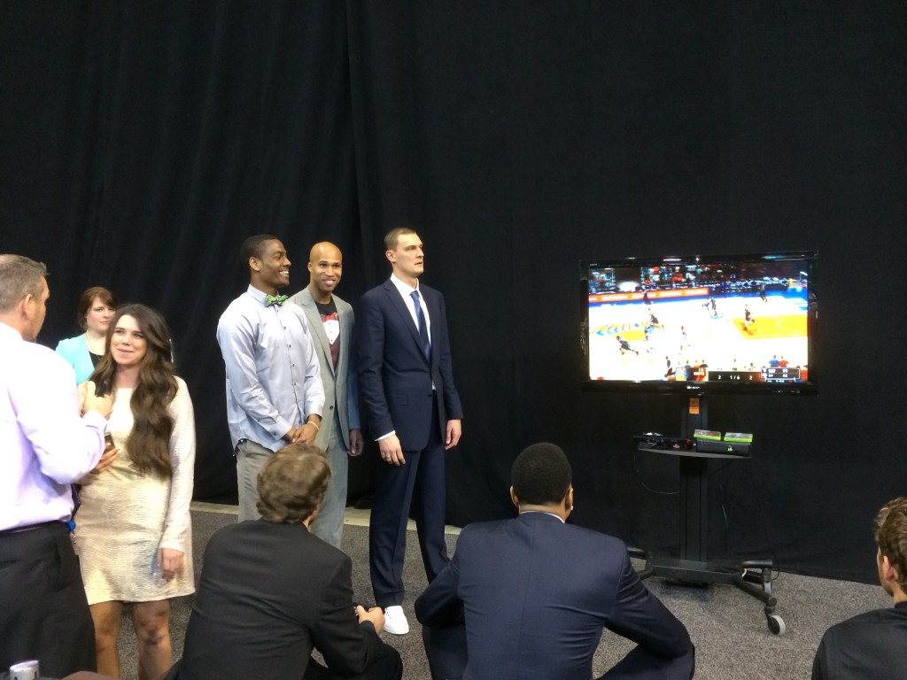 Alec Burks, Richard Jefferson, and Andris Biedrins laugh as Brandon Rush plays NBA 2K with someone.